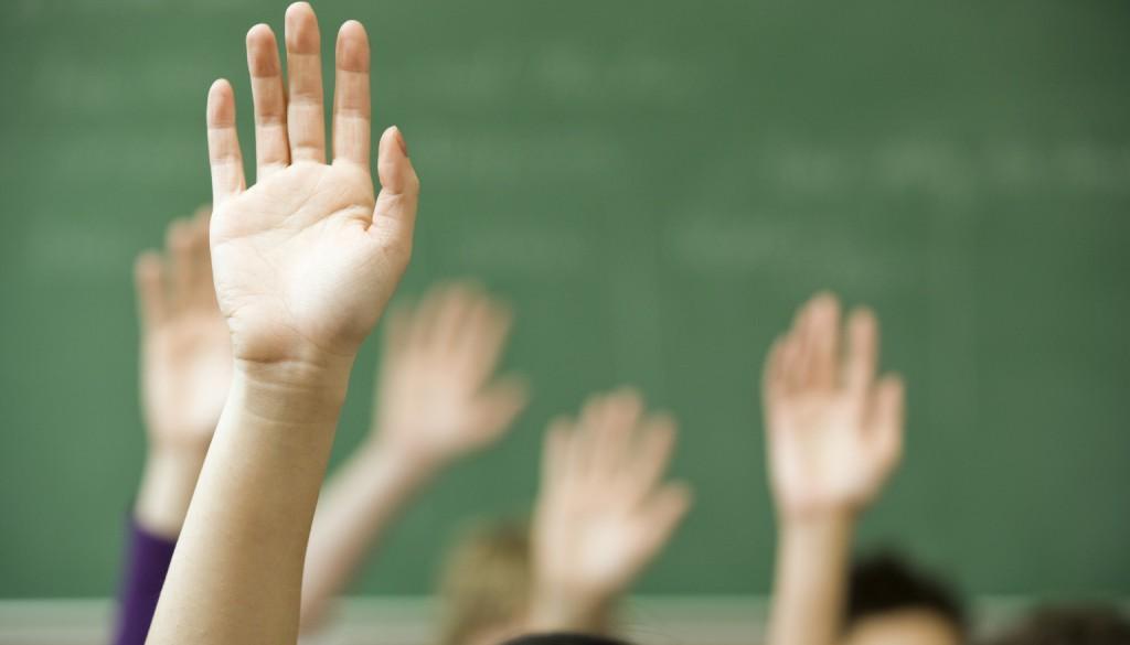 hands raised in class against blackboard
